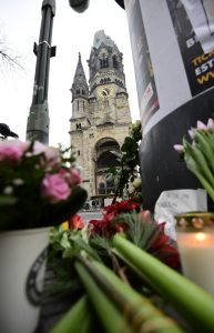 "Flowers are placed on December 20, 2016 at the site where a truck crashed into a Christmas market near the Kaiser-Wilhelm-Gedaechtniskirche (Kaiser Wilhelm Memorial Church) in Berlin. German police said they were treating as ""a probable terrorist attack"" the killing of 12 people when the speeding lorry cut a bloody swath through the packed Berlin Christmas market. / AFP PHOTO / Tobias SCHWARZ"